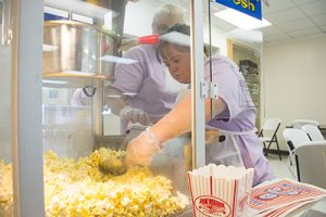 The Gracie Center, Grace scoops and measures popcorn for serving bags.